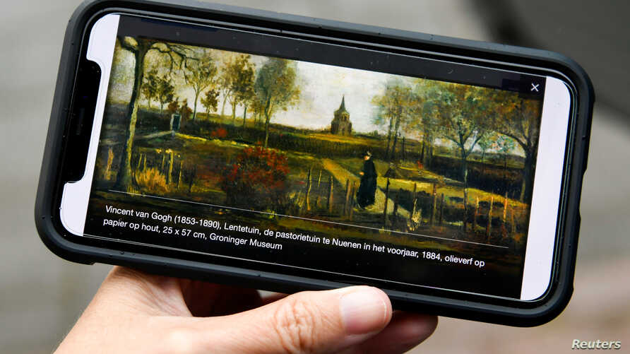 "FILE - A person holds a mobile phone showing ""The Parsonage Garden at Nuenen in Spring 1884,"" a painting by Vincent Van Gogh that was stolen, outside the Singer Laren Museum, where it was displayed, in Laren, Netherlands, March 30, 2020."