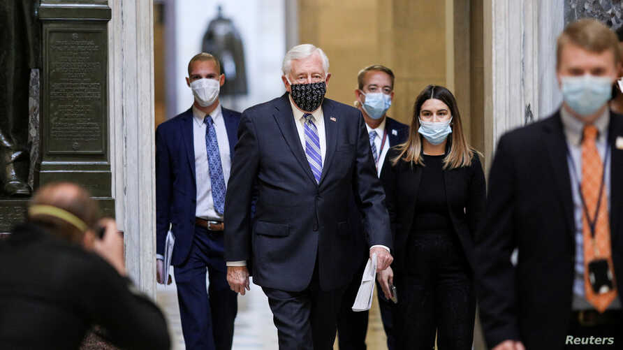 FILE - U.S. House Democratic Majority Leader Steny Hoyer, center, wears a face mask as he walks, accompanied by others, to the House Chamber ahead of a vote, on Capitol Hill in Washington, April 23, 2020.