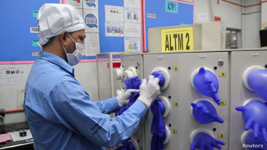 FILE - A worker inspects newly-made gloves at Top Glove factory in Klang, Malaysia, March 3, 2020. (Top Gloves/Anas Zakwan/handout via Reuters)