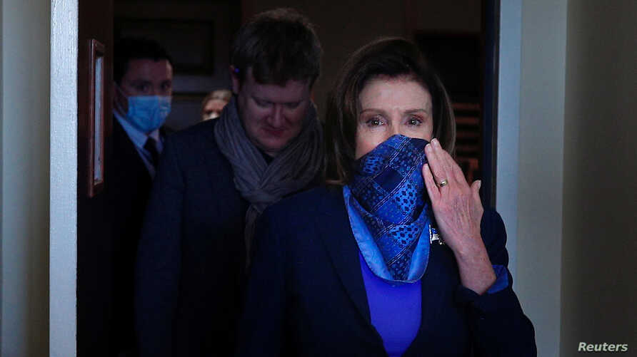 FILE - House Speaker Nancy Pelosi, her face partially covered to protect against the coronavirus, leaves after a news conference at the U.S. Capitol in Washington, April 21, 2020.