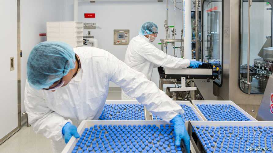 Lab technicians load vials of investigational coronavirus disease (COVID-19) treatment drug Remdesivir at a Gilead Sciences facility in La Verne, California, March 18, 2020.