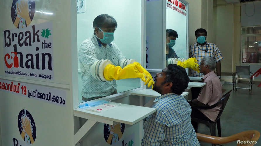 Medical staff members of a government-run medical college collect swabs from people to test for coronavirus disease (COVID-19) at a newly installed Walk-In Sample Kiosk in Ernakulam in the southern state of Kerala, India, April 6, 2020.