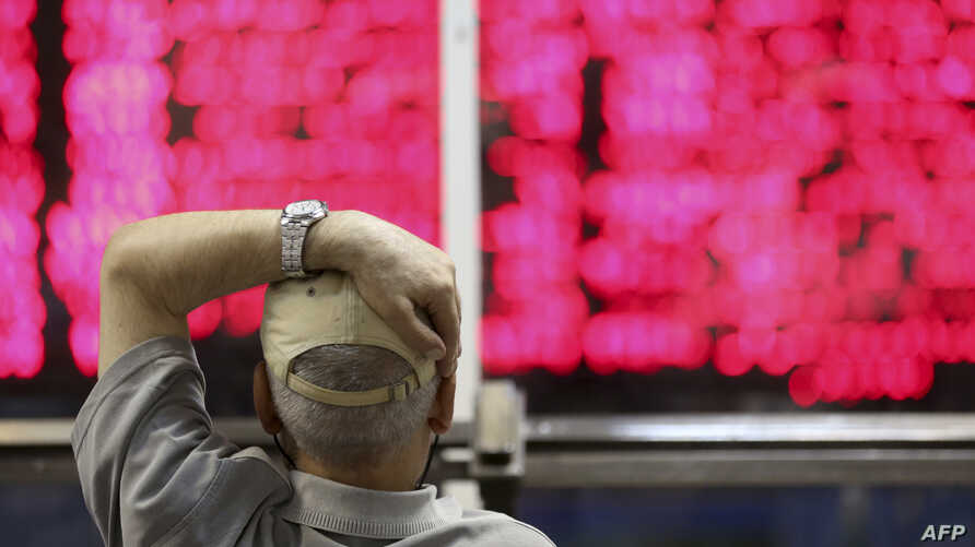 An Iranian man monitors the stock market at Tehran Stock Exchange on July 1, 2019. (Photo by ATTA KENARE / AFP)