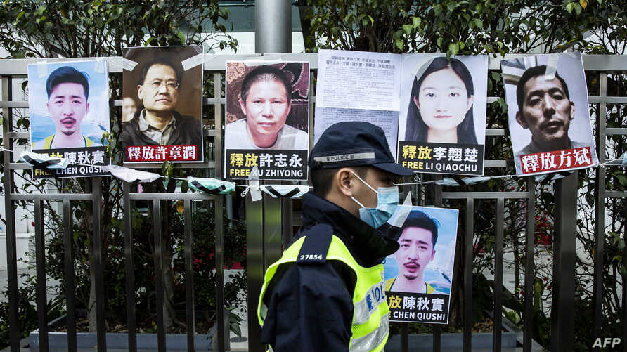 A police officer walks past placards of detained rights activists taped on the fence of the Chinese liaison office in Hong Kong…
