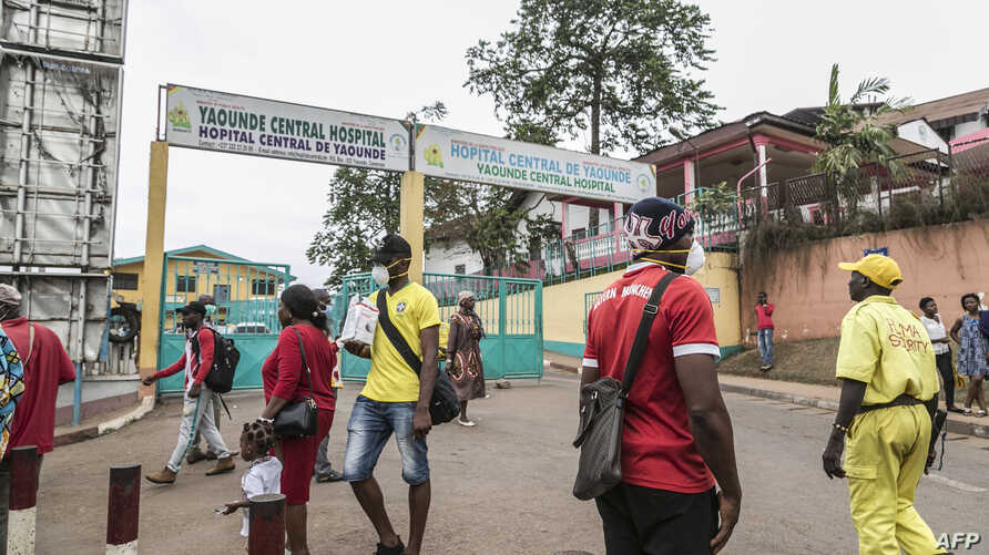 Some people wear masks as they walk by the entrance to the Yaounde General Hospital in Yaounde on March 6, 2020 as Cameroon has…