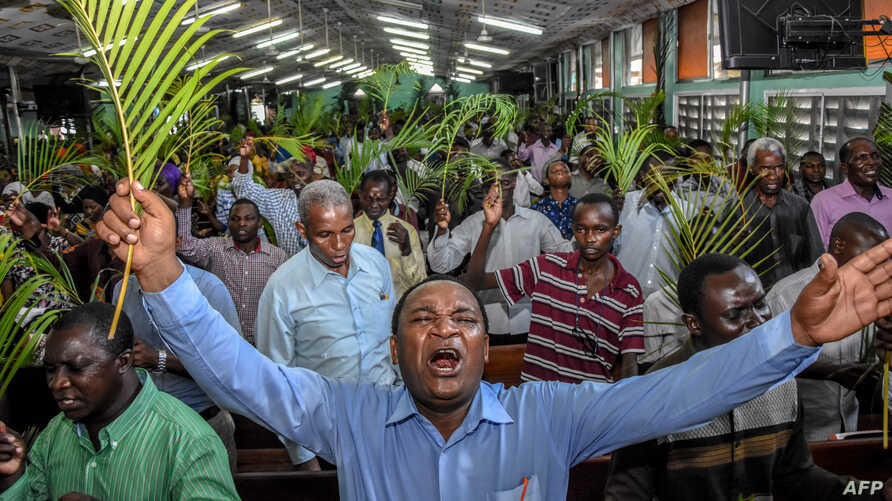Believers pray without taking social distancing during a Palm Sunday mass at the Full Gospel Bible Fellowship Church in Dar es…