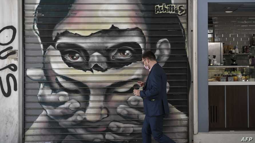 A man wearing a protective facemask walks past a grafitti by greek street artist Achilles in central Athens on May 8, 2020. …