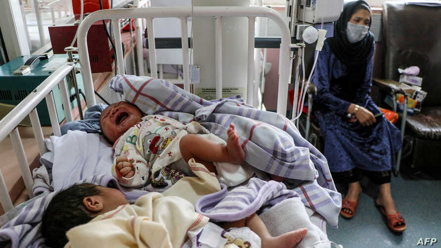 A woman (R) sits next to newborn babies who lost their mothers following a suicide attack in a maternity hospital, in Kabul on…