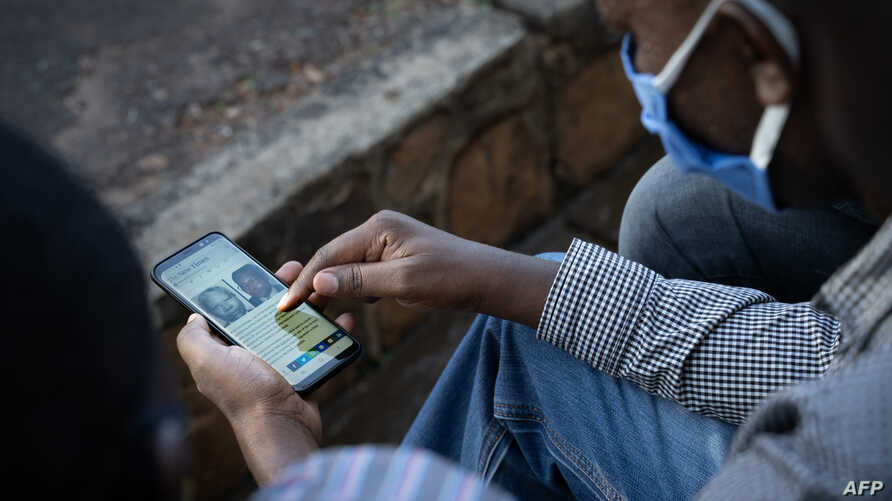 A man looks at his smartphone in Kigali, Rwanda, on May 18, 2020, showing the article on The New Times of the arrest of…
