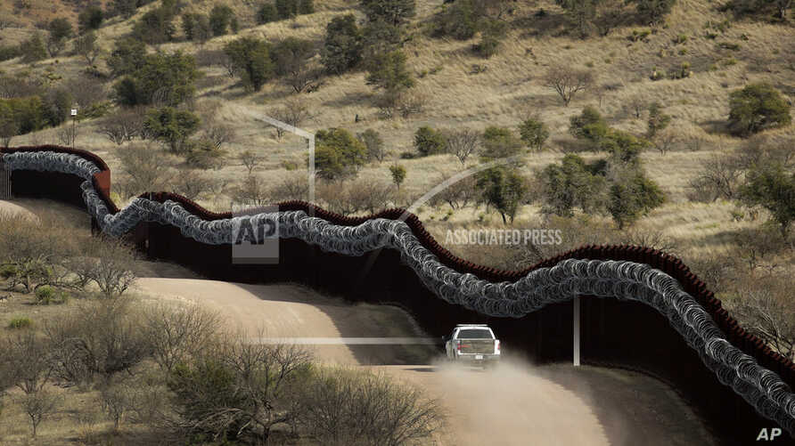 FILE - This March 2, 2019, file photo, shows a Customs and Border Control agent patrolling on the US side of a razor-wire…