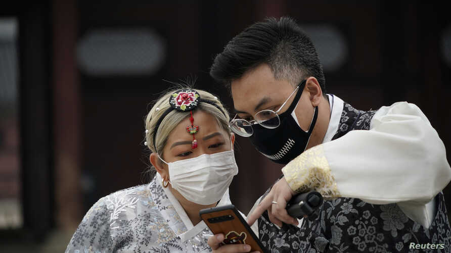 A couple in Korean traditional costumes, Hanbok, wearing masks to prevent contacting the coronavirus, looks at a mobile phone…