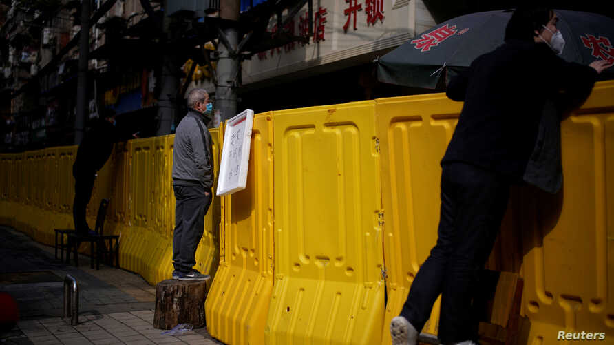Residents wearing face masks pay for groceries by standing on chairs to peer over barriers set up to ring fence a wet market on…