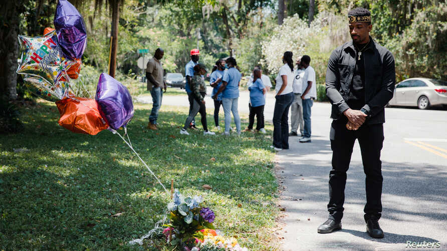 A man stands next to the memorial for Ahmaud Arbery, at the place where he was shot and killed in February after being chased…