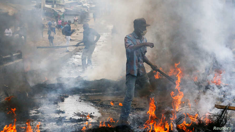 A resident attempts to clear burning tyres used as barricades during clashes between traders and riot police following…