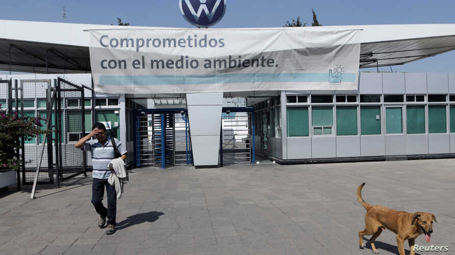FILE PHOTO: An employee leaves the Volkswagen (VW) plant as the company temporarily closes its factories in Mexico amid growing…