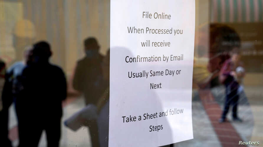 FILE - People who lost their jobs are reflected in the door of an Arkansas Workforce Center as they wait in line to file