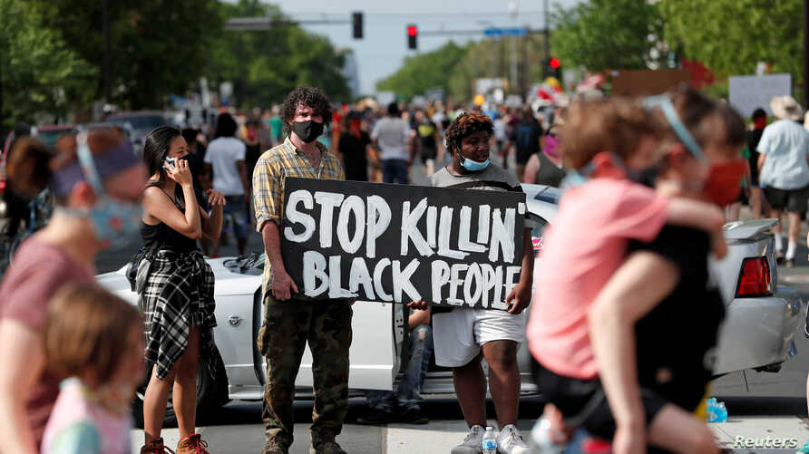 Protesters gather at the scene where George Floyd, an unarmed black man, was pinned down by a police officer