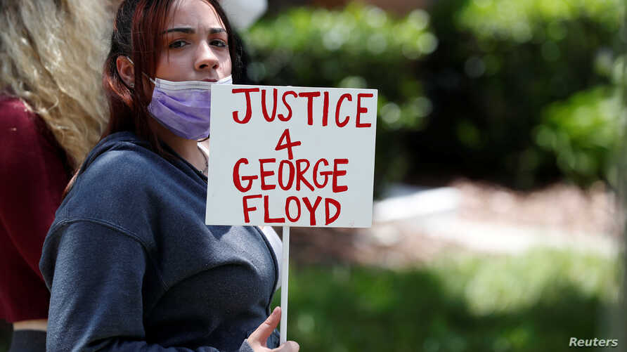 A protester holds a sign outside the Florida home of former Minneapolis police officer Derek Chauvin, who was recorded with his…