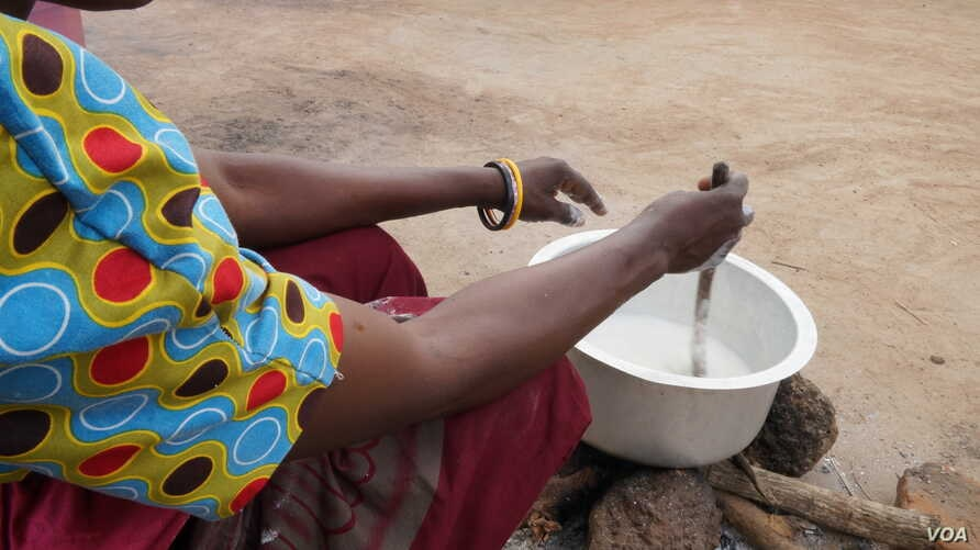 A mother cooking porridge for her children in Dowa district, Malawi. In some families the new school home feeding programs is helping suppliment family food. (Lameck Masina/VOA)