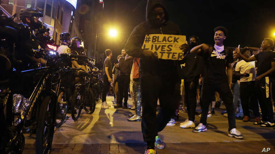 Protesters hold signs and walk past a line of police in downtown Columbus, Ohio, May 28, 2020.