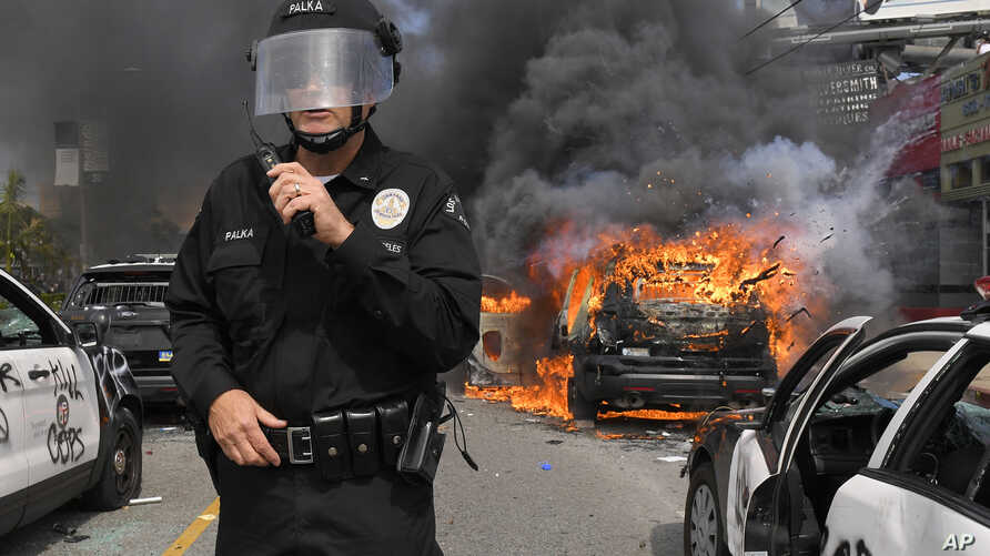 Los Angeles Police Department commander Cory Palka stands among several destroyed police cars as one explodes while on fire