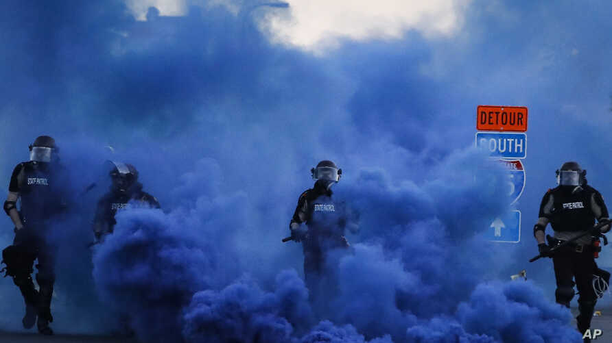 Police in riot gear walk through a cloud of blue smoke as they advance on protesters near the Minneapolis 5th Precinct