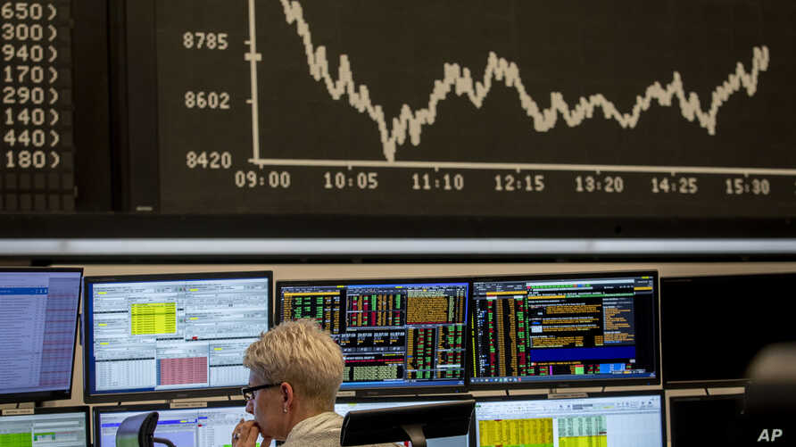 FILE - A broker watches her screens under the curve of the German stock index DAX in Frankfurt, Germany.
