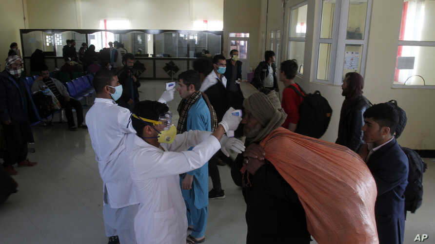 FILE - Afghan health workers measure the temperature of Afghan refugees to screen for coronavirus as they enter Afghanistan at the Islam Qala border crossing with Iran, in the western Herat Province, March 18, 2020.