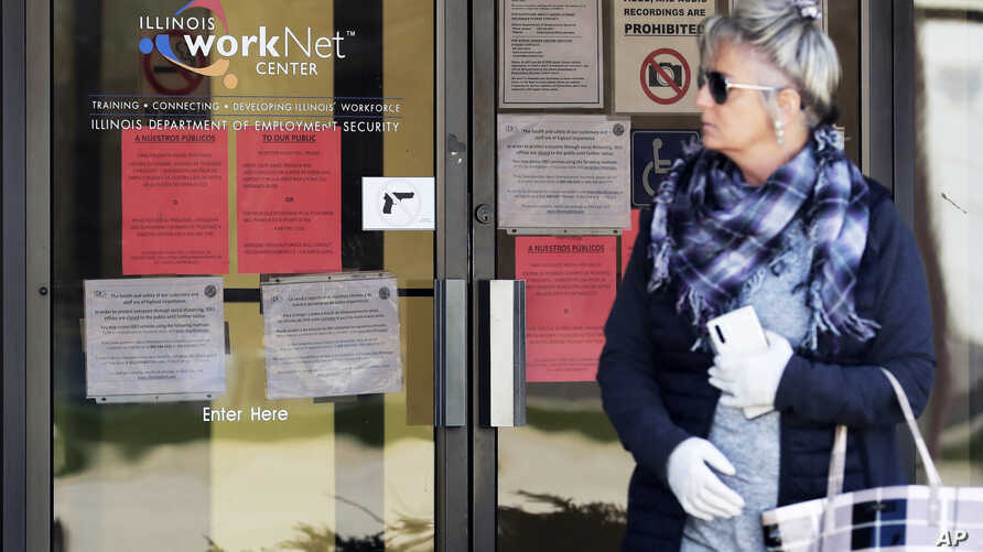 A woman looks to get information about job application in front of IDES (Illinois Department of Employment Security) WorkNet center