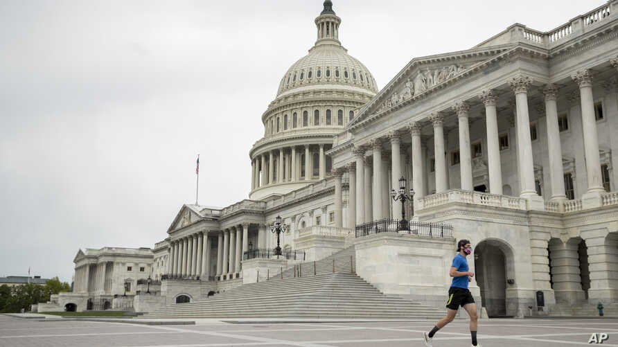 A man wearing a mask depicting American flags jogs past the U.S. Capitol Building, Tuesday, April 28, 2020, in Washington. The…
