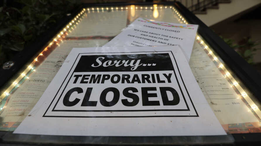 FILE - In this April 28, 2020 file photo, a closed sign is posted at a restaurant along the River Walk in San Antonio.  Banks…