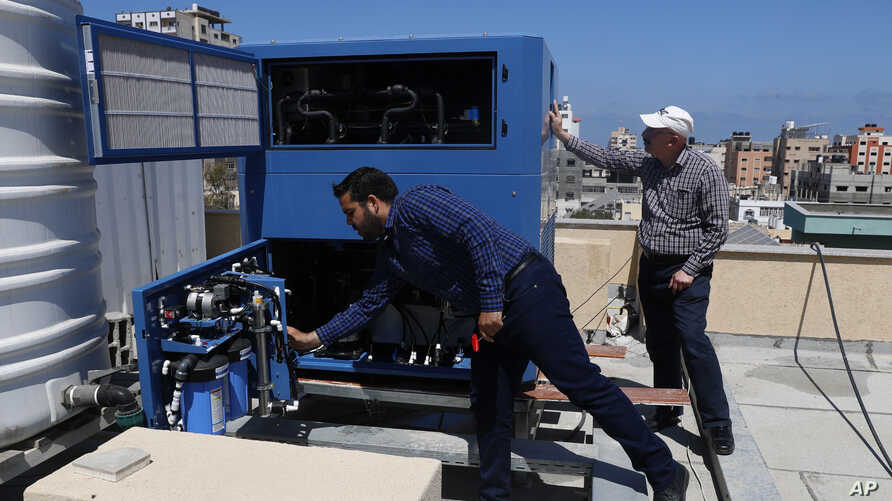 In this Thursday, April 30, 2020 photo, Palestinian engineer Raed Nakhal from Palestine Children Relief Fund, right, and…