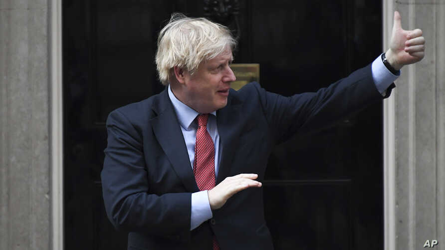 """Britain's Prime Minister Boris Johnson joins in the applause on the doorstep of 10 Downing Street in London during the weekly """"Clap for our Carers"""" Thursday, May 7, 2020."""