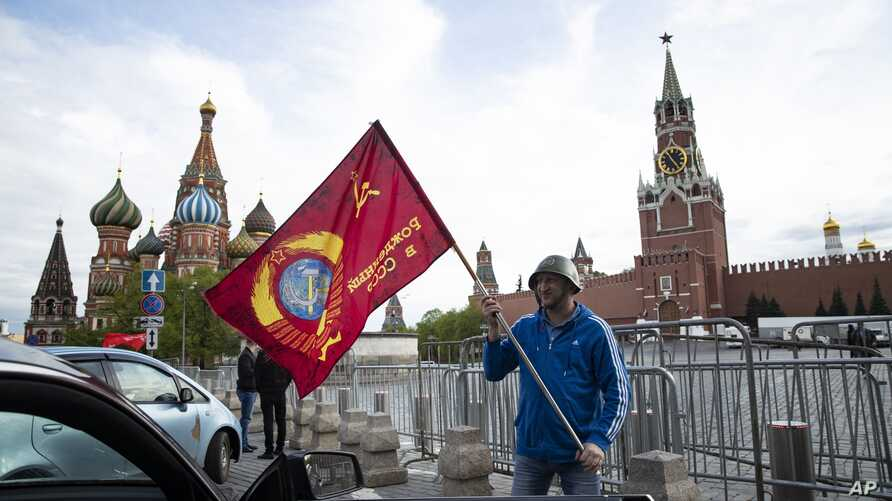 A man poses for a photo with a red flag in front of the closed Red Square during the 75th anniversary of the Nazi defeat in…