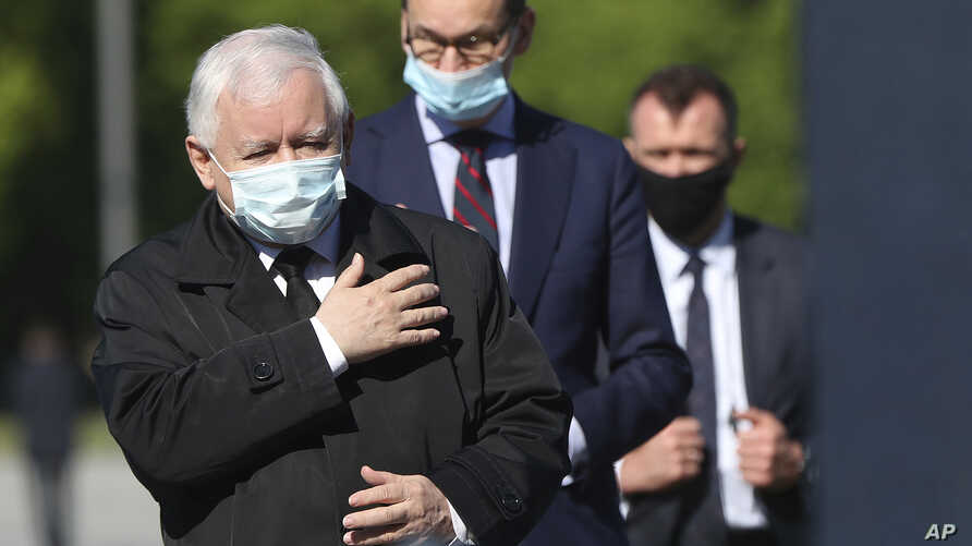 Poland's ruling party leader Kaczynski, left, and PM Morawiecki, center, pray at the monument to the late President Lech Kaczynski, the party leader's twin, killed with 95 others in a plane crash April 10, 2010 in Russia, in Warsaw, May 10, 2020.