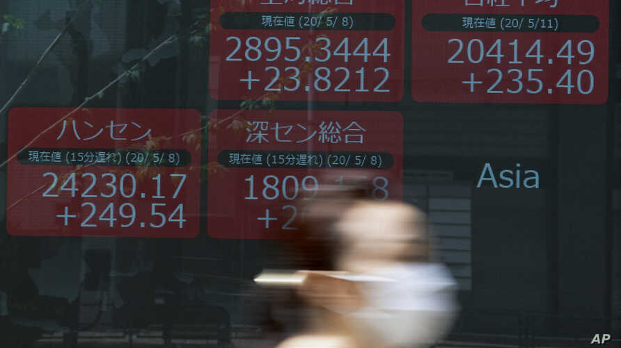 A woman wearing a face mask walks past an electronic stock board showing Japan's Nikkei 225 and other Asian countries' index at…