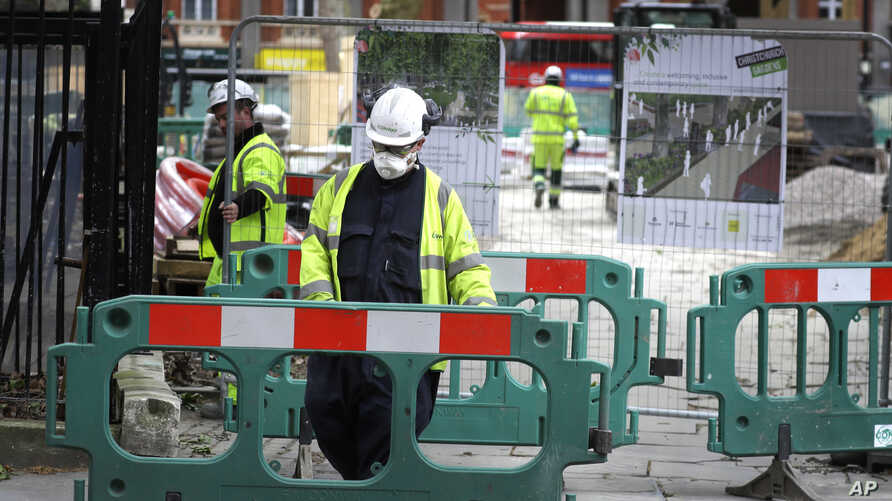 Construction workers social distance as they work in London as the country is in lockdown to help stop the spread of…