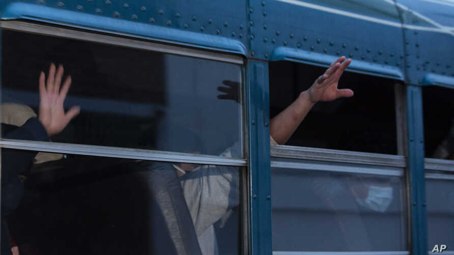 FILE - In this May 4, 2020, file photo, Guatemalans deported from the U.S., wave from a bus after arriving at La Aurora airport in Guatemala City.