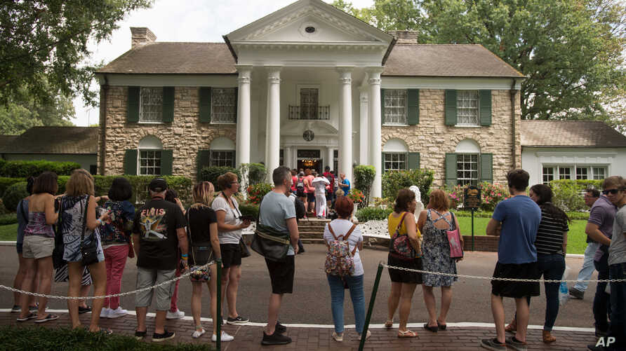 FILE - Fans wait in line outside Graceland, Elvis Presley's Memphis home, in Memphis, Tennessee, Aug. 15, 2017.