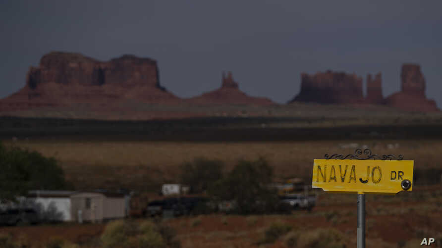 In this April 30, 2020, photo, a sign marks Navajo Drive as Sentinel Mesa, homes and other structures in Oljato-Monument Valley…