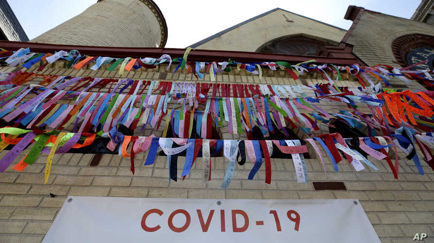 Ribbons hang in remembrance of victims of the coronavirus pandemic outside the Grant African Methodist Episcopal Church, Tuesday, May 19, 2020, in Boston.