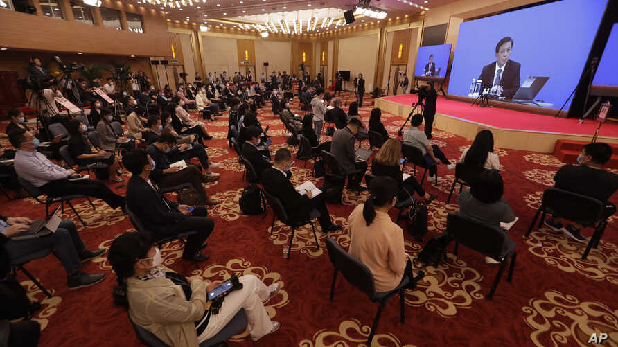 Journalists attend a news conference by Zhang Yesui, a spokesman for the National People's Congress, broadcast remotely to the media center on the eve of the annual legislature opening session in Beijing on Thursday, May 21, 2020.