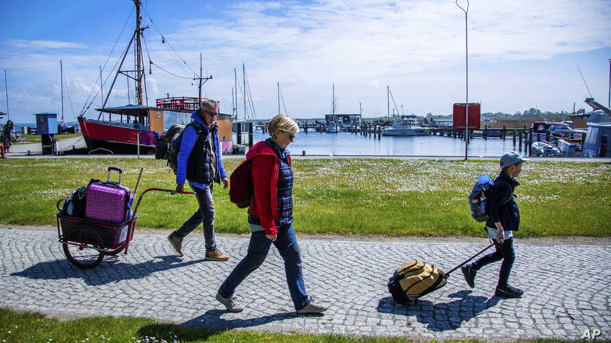 Tourists with backpacks and suitcases arrives at the port of Kloster on the Baltic island Hiddensee in Vitte, Germany