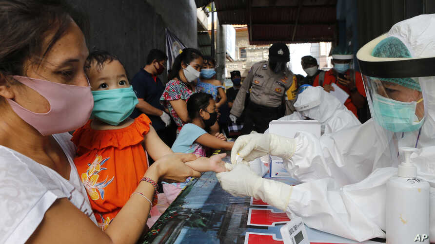 A mother holds her daughter to receive a coronavirus antibody test from health workers at a village in Bali, Indonesia