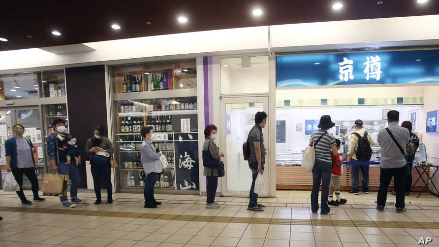 People wearing face masks to protect against the spread of the new coronavirus keep social distancing as they wait to buy sushi…