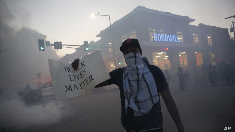 """A demonstrator displays a """"Black Lives Matter"""" sign, May 28, 2020, in St. Paul, Minn."""