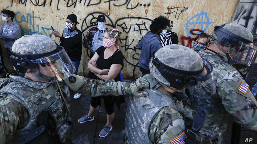 National Guard personnel return to their defensive position as protesters make room for them to fall back following a confrontation on East Lake Street, May 29, 2020, in St. Paul, Minn.