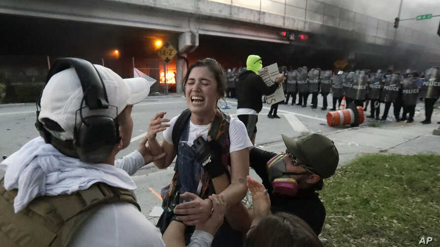 Protesters help a woman who was hit in the throat with a rubber bullet during a demonstration next to the city of Miami Police.