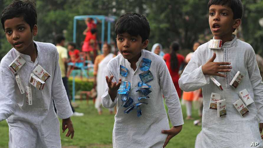 FILE - Children wear strings of cigarette and chewable tobacco and rehearse for a play on World No Tobacco Day in Gauhati, India.