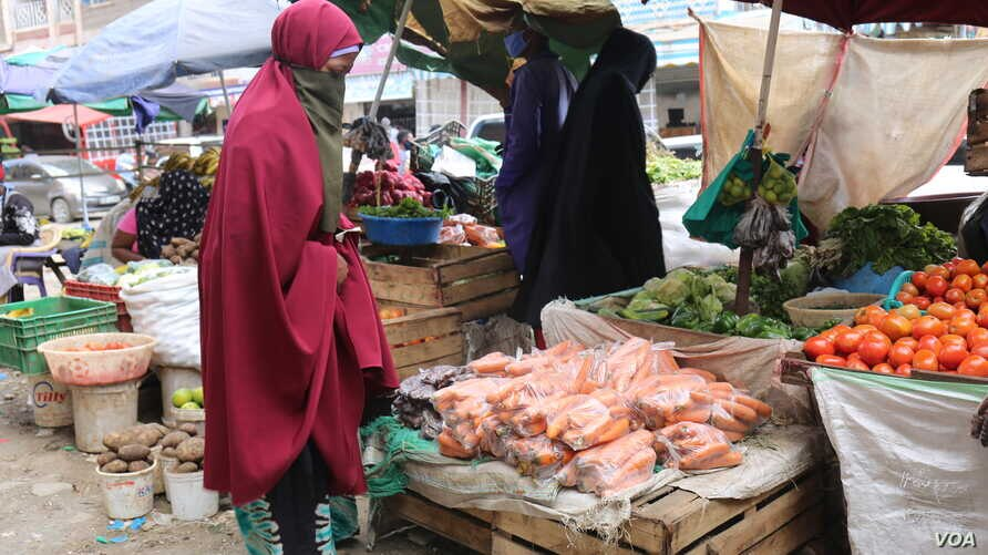 A woman buys vegetable from a local vendor in Eastleigh Nairobi. The neighborhood is under lockdown after spike in COVID19 cases